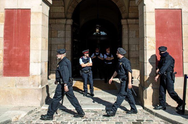 Varios policías nacionales pasan por delante de agentes de los...
