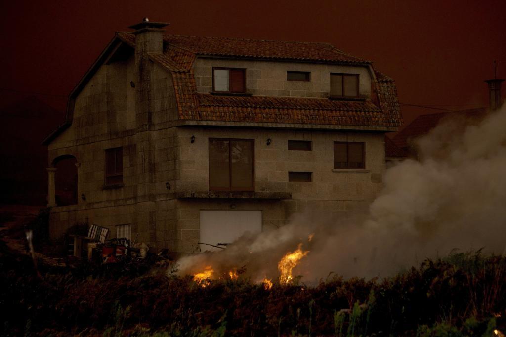 Las llamas acercándose a las viviendas situadas en la parroquia en Chandebrito, perteneciente al municipio pontevedrés de Nigrán.