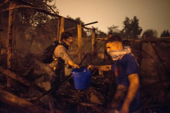 Ciudadanos ayudan a sofocar con cubos de agua uno de los focos declarados en el centro de la ciudad de Vigo.