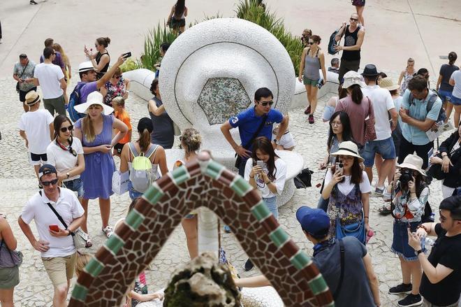 Numerosos turistas paseaban esta mañana por la zona monumental del Park Güell de Barcelona, en agosto.