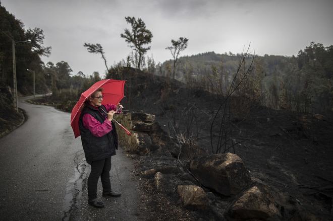 Una vecina de Nigran, en Pontevedra, contempla el terreno arrasado por el fuego.