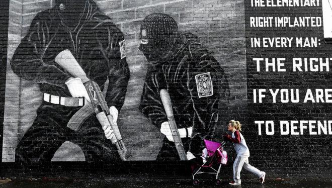 Una mujer empuja un cochecito delante de un mural paramilitar en...