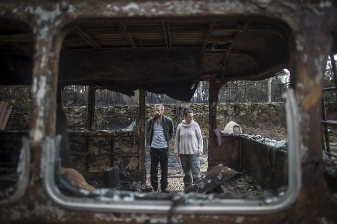 Harry y Elena observan los restos calcinados del que fue su hogar.