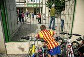 """Un niño en una escuela frente a un cartel que dice: """"Por un país de..."""