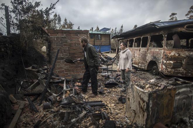 Una pareja recorriendo los restos de su casa calcinada por los incendios.