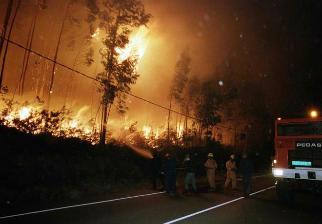 Brigadas de la lucha contra incendios intentan controlar las llamas del incendio en la carretera.