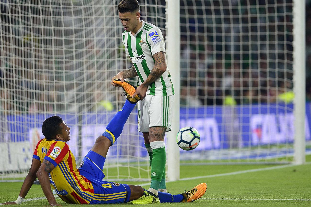 El jugador del Betis Arnaldo Sanabria, ayuda a estirar al jugador del Valencia CF Jeison Murillo, durante el partido de liga celebrado en el estadio Benito Villamarín de Sevilla.