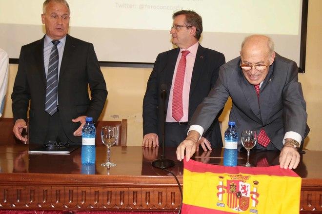 , JoseJosep Bou (a la izquierda) al inicio de su conferencia mientras José Torné, presidente del Foro coloca una bandera española en la mesa.