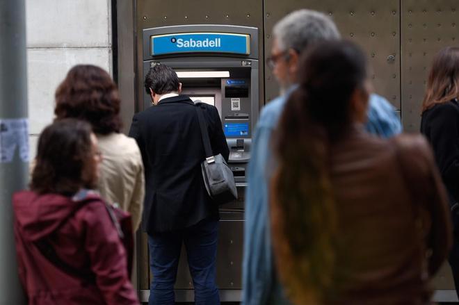 Un grupo de personas retira dinero de un cajero, ayer, en Barcelona.