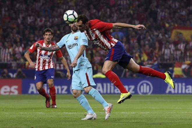 Diego Godín despeja un balón ante Leo Messi.