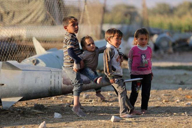 Niños sirios juegan con un misil abandonado, en un campo de refugiados del este de Guta (periferia rural de Damasco).