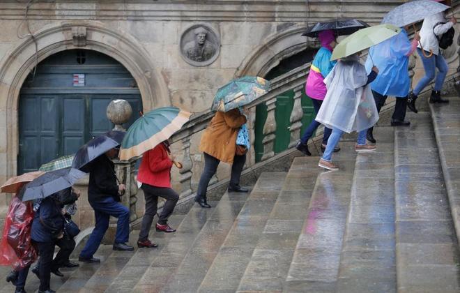 Varios turistas se protegen de la lluvia mientras suben a la Plaza de...