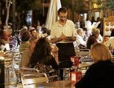 Un camarero anota una comanda en la terraza de un establecimiento.
