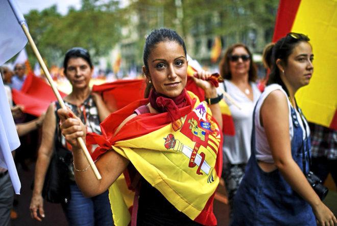 Una mujer pasea ataviada con una bandera de España en la...