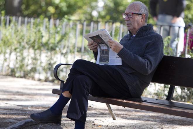 Un jubilado lee un periódico en el madrileño parque del Oeste.