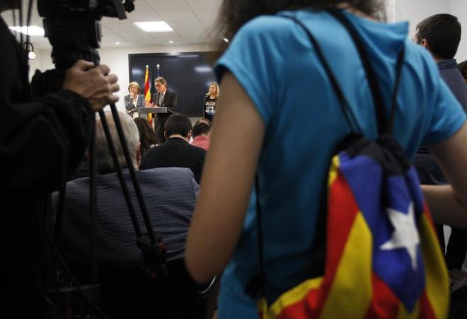 Una asistente a una rueda de prensa de Artur Mas con una mochila con...