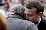 Emmanuel Macron se abraza a una de las víctimas de los atentados, este lunes, cerca del Bataclan.