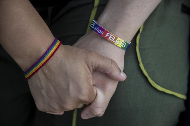 Dos manos entrelazadas con sendas pulseras en pro del colectivo LGBI.