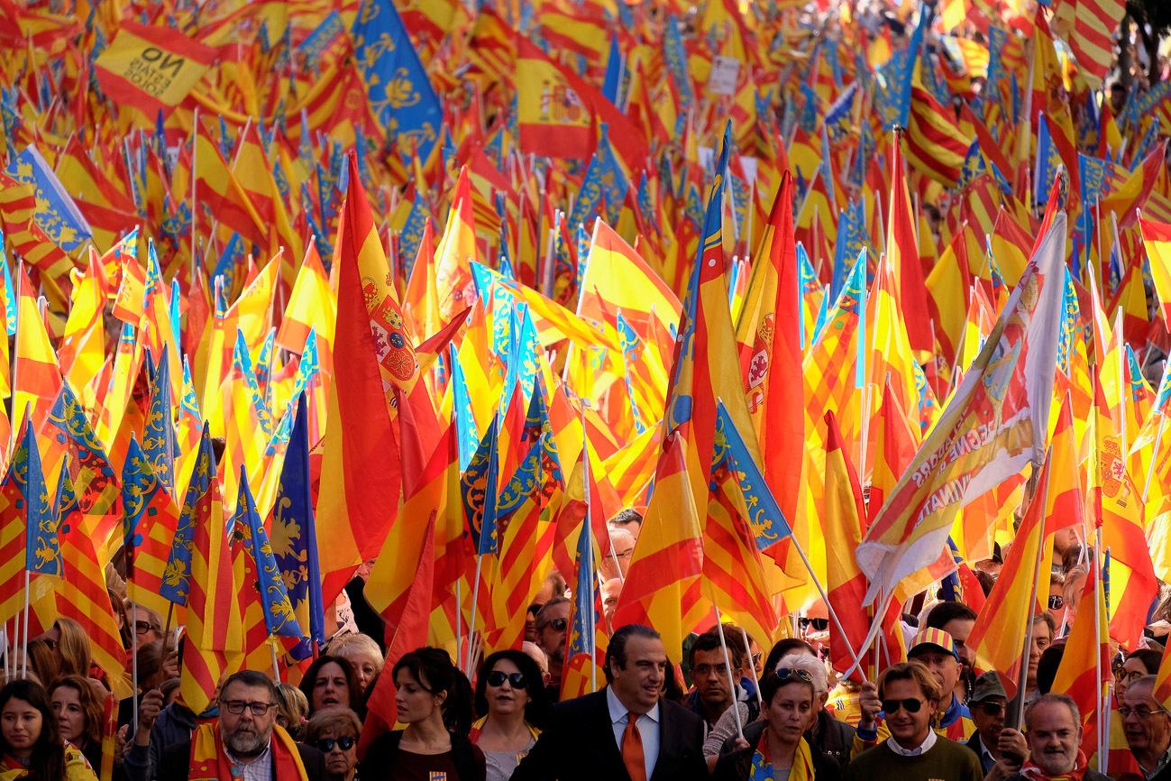 Manifestantes agitan banderas españolas y valencianas durante una...