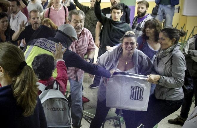 Un grupo forcejea con un policía nacional por una urna durante el...