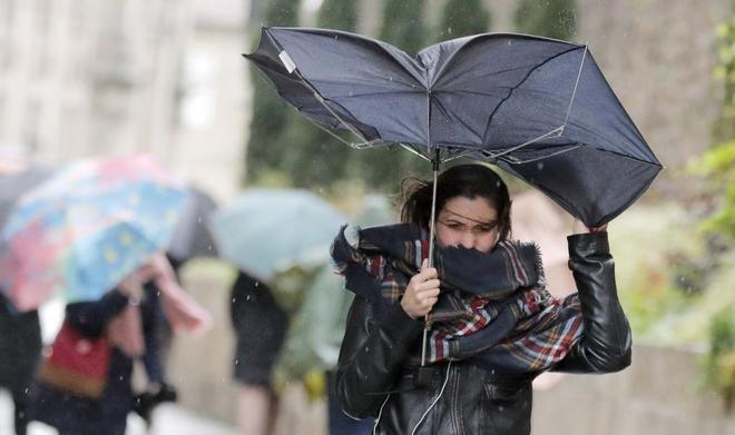 Una mujer combate el viento y las lluvias en Santiago de Compostela
