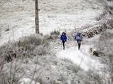 Dos peregrinos caminan cerca del puerto de O Poio, en Cebreiro (Lugo)