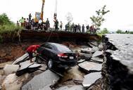 Oficiales tailandeses sacan un vehículo de una carretera derrumbada por las inundaciones.