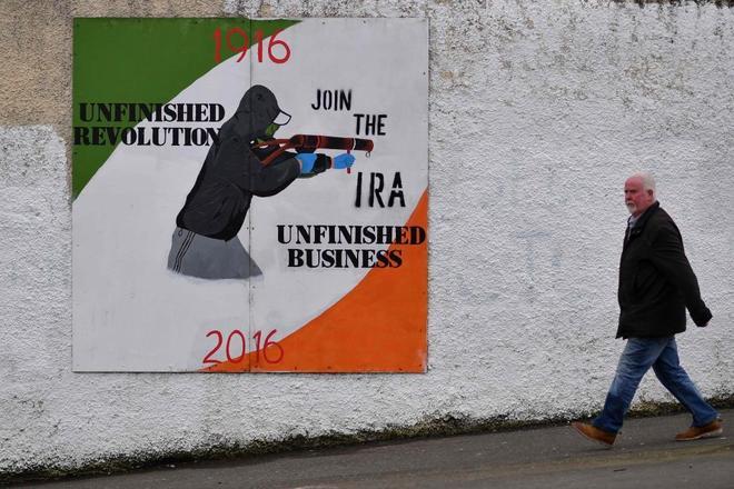Un hombre camina junto a un mural que celebra el centenario del IRA situado en el Bogside de Derry.