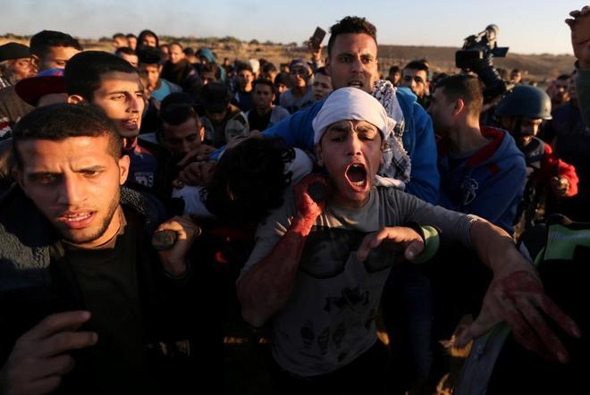 Jóvenes palestinos evacuan a un herido durante las protestas del día de la Ira.