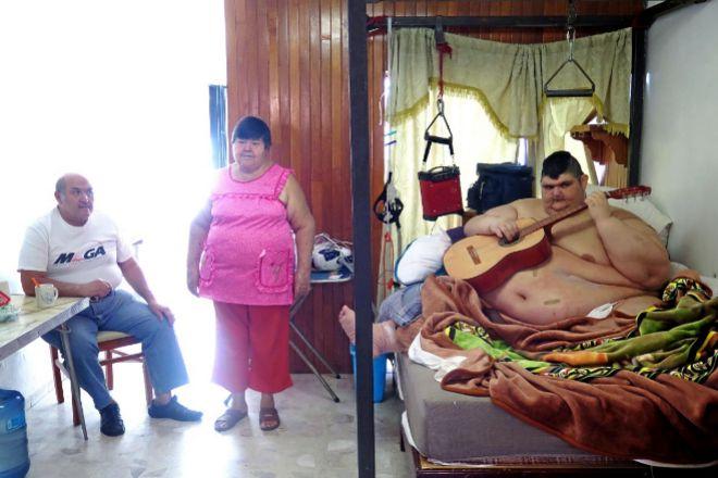 Juan Pedro con sus padres en su casa de Guadalajara (México). Con seis años ya pesaba 60 kilos. A los 17 ya eran 240. Con 23 años, 335 kilos. Su marca mundial: 594,8 kilos. «No sé cómo sería la vida sin ser gordo», dice el joven, que vive (obligado) en la cama.