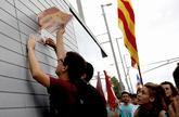 Un grupo de estudiantes arranca pegatinas con la bandera española en...