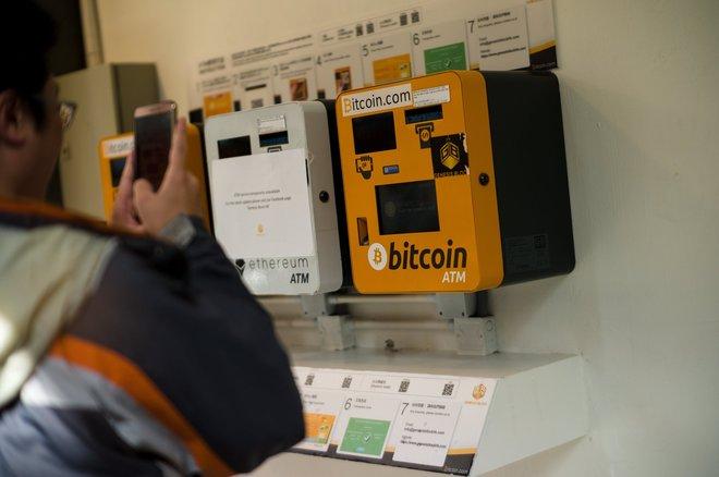Un hombre fotografía un cajero de bitcoin en Wanchai (Hong Kong).