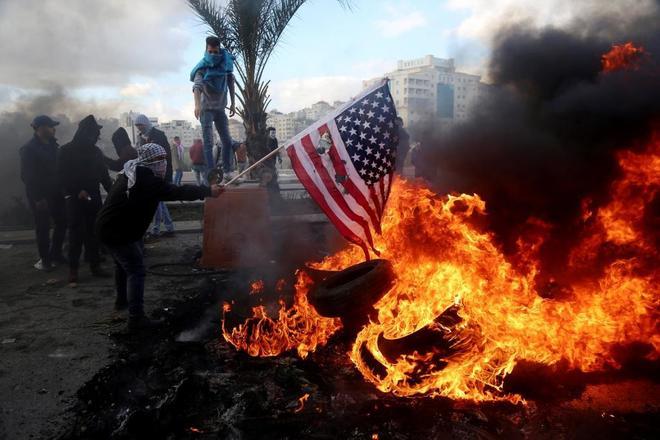 Un manifestante palestino quema una bandera estadounidense durante un enfrentamiento con tropas israelíes en Ramala