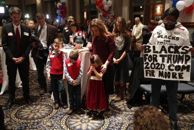 Simpatizantes del candidato a senador republicano Roy Moore rezan durante la noche electoral en Montgomery, Alabama.