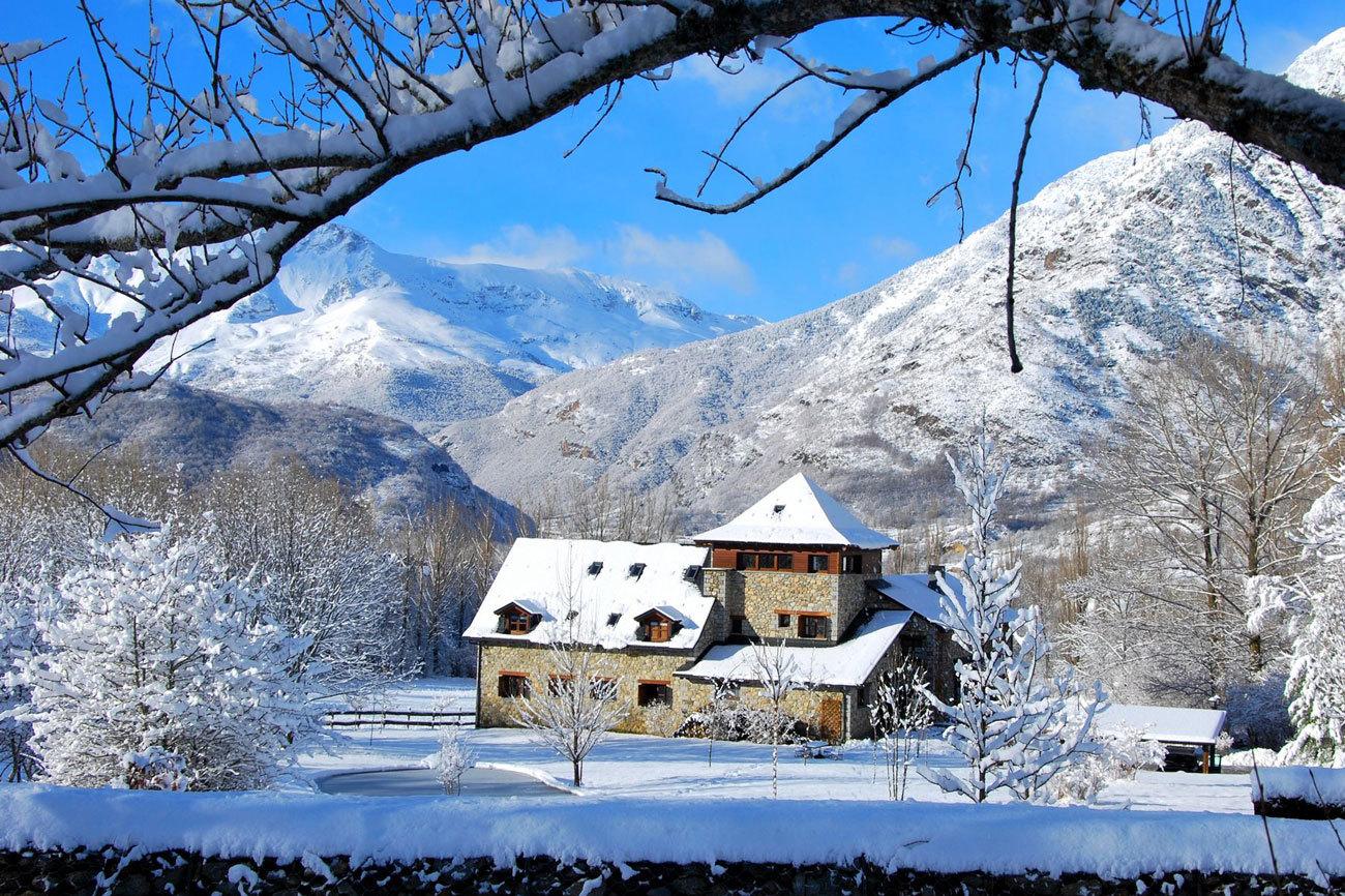 """A los pies del Aneto, el pico con más altitud de los Pirineos (3.404 metros), nace el valle de Benasque, en Huesca. Prados y bosques infinitos a tan sólo seis kilómetros de la estación de esquí alpino de Cerler. El hotel rural Selba D'Ansils ofrece una de las mejores opciones para disfrutar del invierno en esta parte de la región. Habitaciones desde <strong>125 euros</strong>  con posibilidad de servicio de cenas, menú del día y <em>fondue</em> de quesos. Algunas de las estancias incluyen jacuzzi, hidromasaje, terraza y chimenea. Más información en <a href=""""http://hotelselbadansils.com/"""" target=""""_blank"""">www.hotelselbadansils.com</a>"""