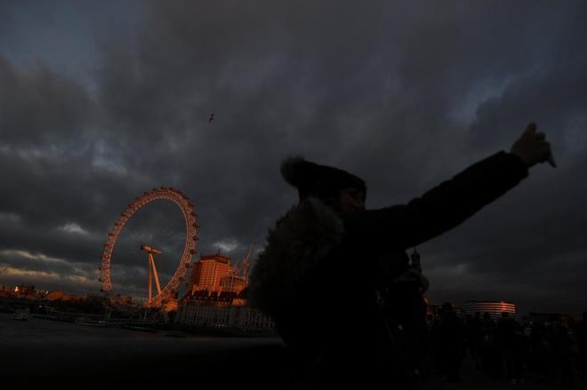 Una persona se fotografía en  el puente de Westminster (Londres), con el London Eye de fondo.