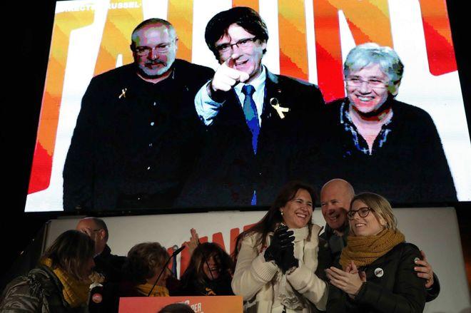 Carles Puigdemont, en la pantalla desde Bruselas, en el acto de cierre de campaña de JxCat