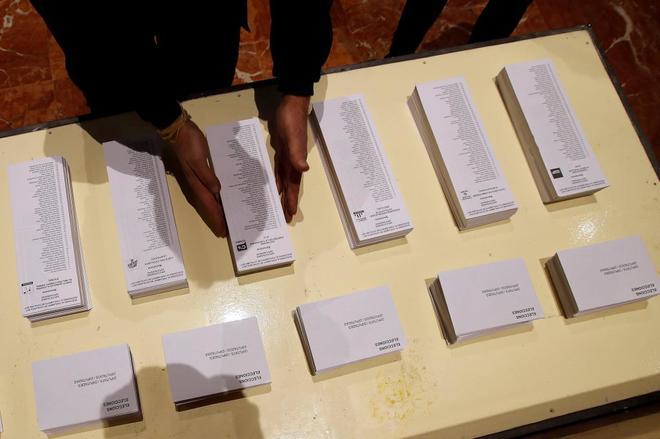 Un operario coloca papeletas electorales en el Ayuntamiento de...