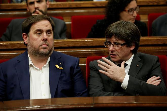 El ex presidente Puigdemont y el ex vicepresidente Junqueras durante una sesión plenaria en el Parlament, en una imagen de archivo.