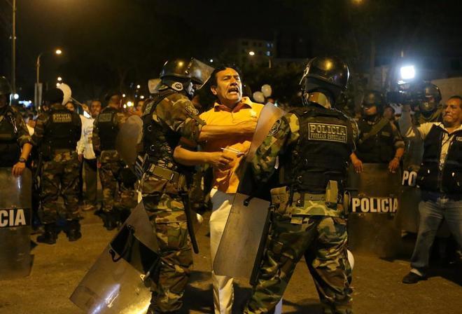 Manifestantes y policía se enfrentan cerca del hospital de Centerio, tras el indulto a Fujimori.