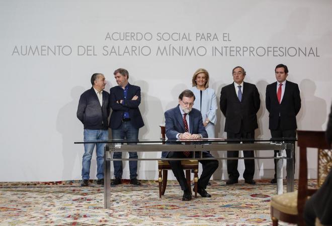El presidente del Gobierno, Mariano Rajoy, firma el acuerdo para subir el Salario Mínimo en presencia de la ministra Fátima Báñez, patronal y sindicatos, ayer en Moncloa.