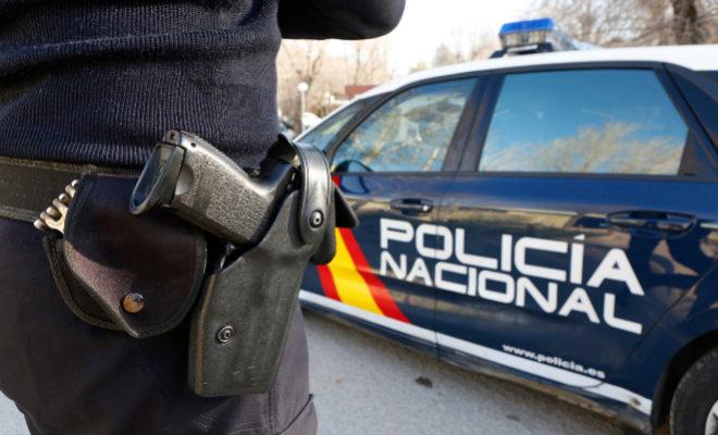 Un agente de la Policía Nacional junto a un coche oficial.