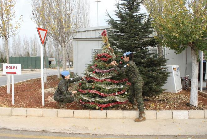 Dos militares decoran un árbol de Navidad en la base Miguel de Cervantes en Marjayún (Líbano)