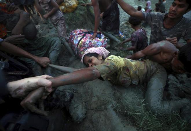 La autora de esta foto tira del brazo de una refugiada rohingya que intenta salir del barro tras cruzar el río Nad, que hace frontera entre Birmania y Bangladesh.
