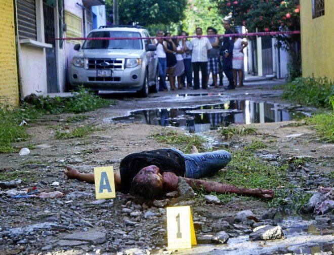 El cuerpo de una mujer asesinada tendido en el suelo, en el barrio de Ciudad Renacimiento, en Acapulco. AFP