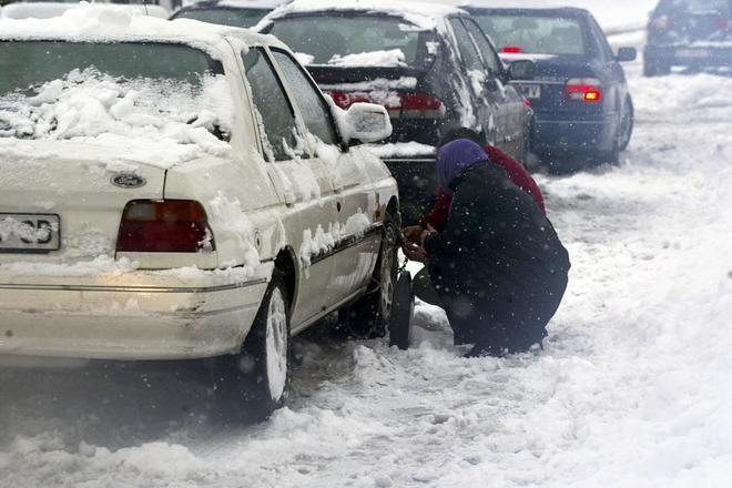 Dos personas colocan cadenas en su vehículo para poder circular durante el temporal de 2004 en Burgos.