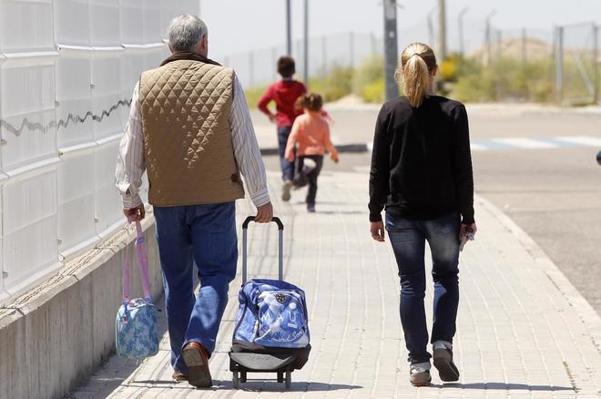 Un padre y una madre llevan la mochilas del colegio de sus hijos
