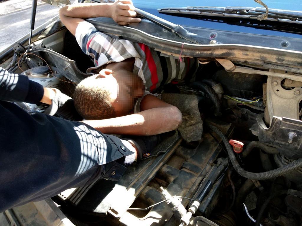 Un policía rescata a una de las personas ocultas en el vehículo.