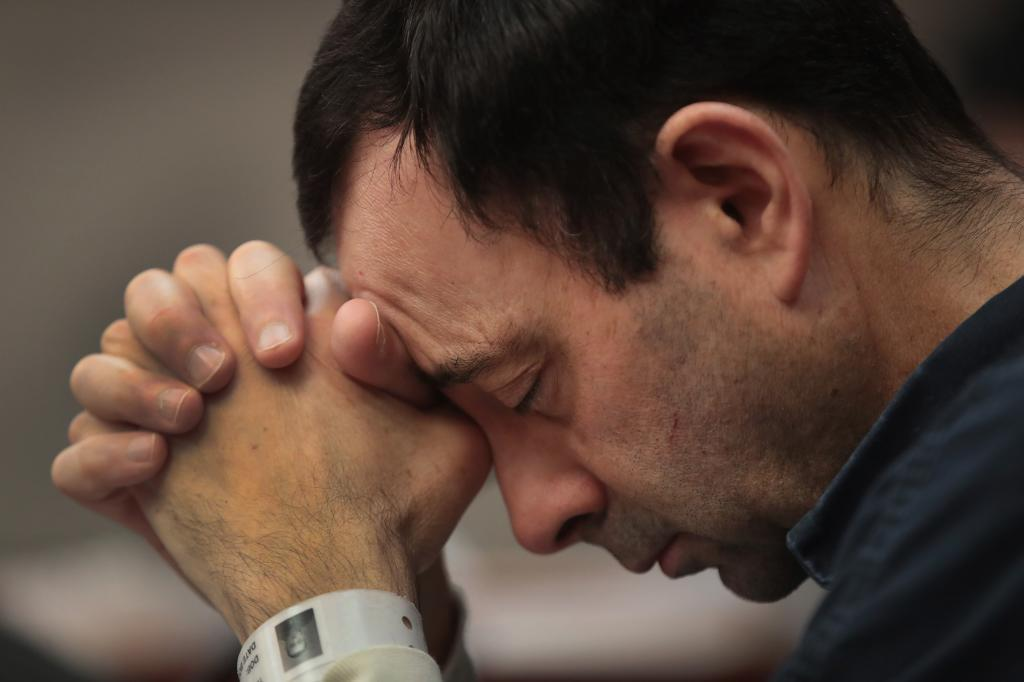 == FOR NEWSPAPERS, INTERNET, TELCOS & TELEVISION USE ONLY == LANSING, MI - JANUARY 16: Larry Nassar listens to victim impact statements prior to being sentenced after being accused of molesting about 100 girls while he was a physician for USA Gymnastics and Michigan State University, where he had his sports-medicine practice on January 16, 2018 in Lansing, Michigan. Nassar has pleaded guilty in Ingham County, Michigan, to sexually assaulting seven girls, but the judge is allowing all his accusers to speak. Nassar is currently serving a 60-year sentence in federal prison for possession of child pornography. Scott Olson/Getty Images/AFP
