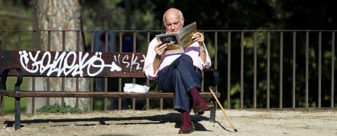 Un jubilado lee una revista sentado en un banco del madrileño Parque del Oeste.